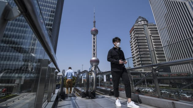 Một người đi bộ đeo khẩu trang qua khu tài chính Lujiazui (Lục Gia Chủy) ở Thượng Hải, Trung Quốc vào Thứ Sáu ngày 20/3/2020.