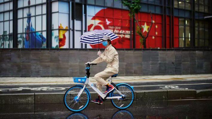 Một người phụ nữ đạp xe trên đường sau khi lệnh phong tỏa được gỡ bỏ tại Vũ Hán ngày 10/4/2020.